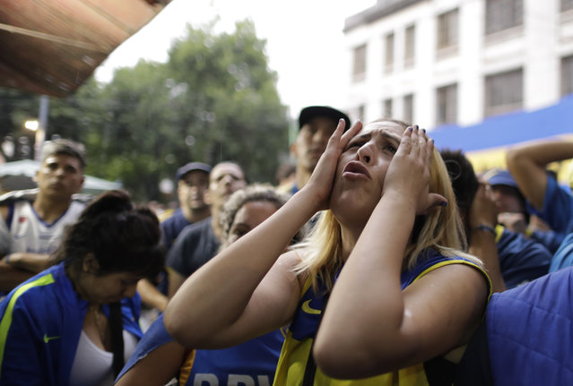A Boca Juniors soccer fan reacts to losing 3-1 to River Plate as she watches on TV the Copa Libertadores final in Buenos Aires, Argentina, Sunday, December 9, 2018. (Photo by Natacha Pisarenko/AP Photo)