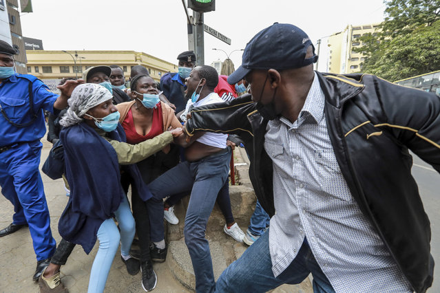 Kenyan activists (L) resist arrest from police officers, as police chased after activists from different social justice centers based in informal settlements, who were marching in protest against police brutality and harassment in their communities on Sab'a Sab'a day (or Seven-Seven), in Nairobi, Kenya, 07 July 2021. Police used tear gas to disperse the protestors and arrested several of them during the protest. The Sab'a Sab'a day commemorates protests and government crackdown on a multi-party democracy movement in the 1990's. (Photo by Daniel Irungu/EPA/EFE)