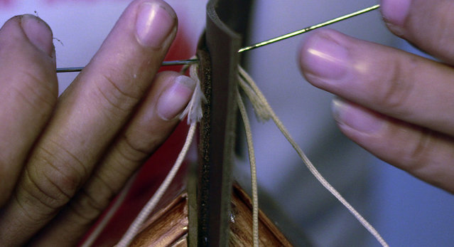 An artisan stitches together patches of leather to make a wallet. (Photo by Rezza Estily/JG Photo)