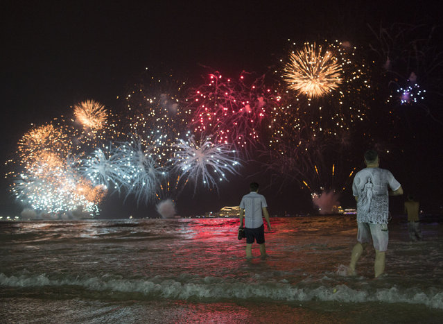People watch the fireworks exploding over Copacabana beach during the New Year's Eve celebrations in Rio de Janeiro, Brazil, Sunday, January 1, 2017. (Photo by Leo Correa/AP Photo)