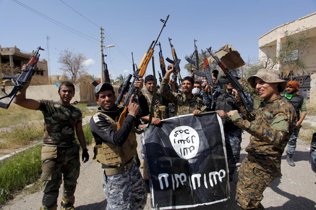 Iraqi security forces and Shi'ite paramilitary fighters hold an Islamist State flag, which they pulled down in Tikrit, March 31, 2015. (Photo by Alaa Al-Marjani/Reuters)