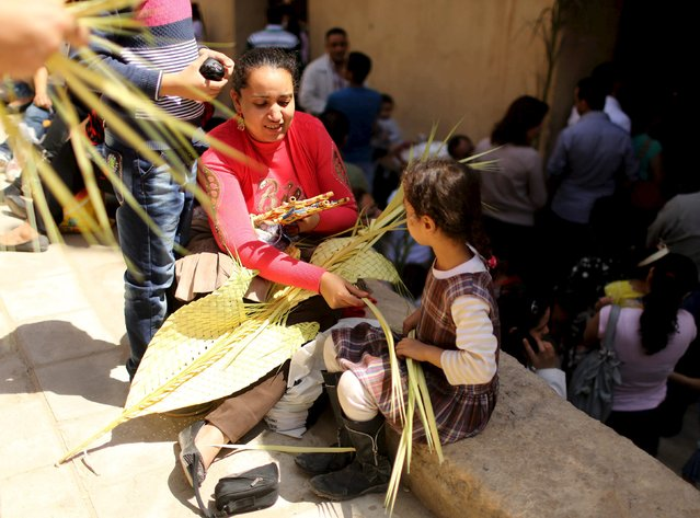 An Egyptian Coptic Christian woman makes palm decoration with her daughter during Palm Sunday inside a Church in Old Cairo, April 5, 2015. (Photo by Asmaa Waguih/Reuters)