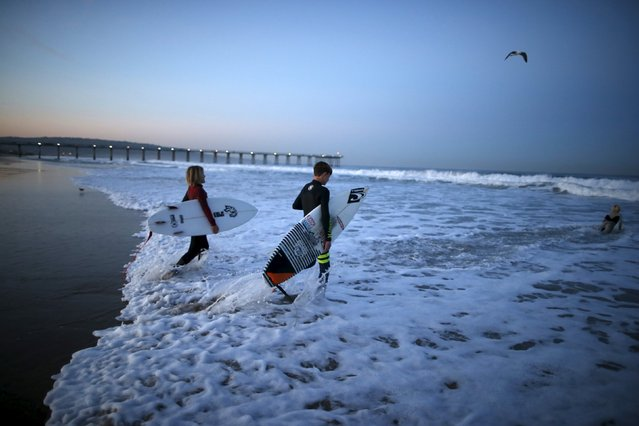 Luke Personius, 12, (R) and Shane Moseley, 13, go surfing before school at sunrise in Hermosa Beach, California March 24, 2015. (Photo by Lucy Nicholson/Reuters)