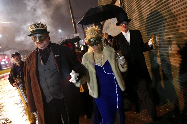 """Chuck Rogers, left, and Kathleen Barrow, inaugural King and Queen of the """"Societe des Champs Elysee"""" lead a crew of costumed revelers to board the Rampart-St. Claude street car line, which just opened last fall, to commemorate the official start of Mardi Gras season, in New Orleans, Friday, January 6, 2017. (Photo by Gerald Herbert/AP Photo)"""
