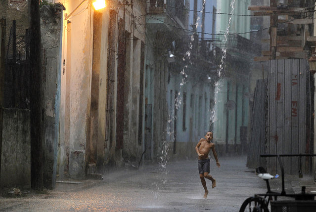 A boy dances in the rain during a heavy tropical shower in a street of Havana, July 2010. (Photo by Desmond Boylan/Reuters)