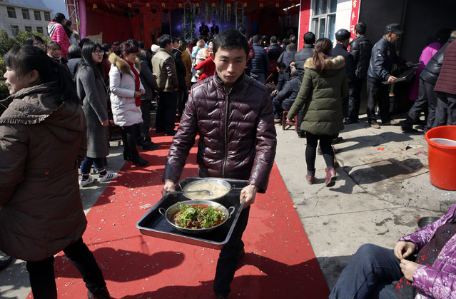 A local villager carries food at a traditional ethnic Tujia wedding feast for about 2000 guests during celebrations marking the Lunar New Year, in Ziqiu town, Changyang county of China's Hubei province, February 15, 2016. (Photo by Jason Lee/Reuters)