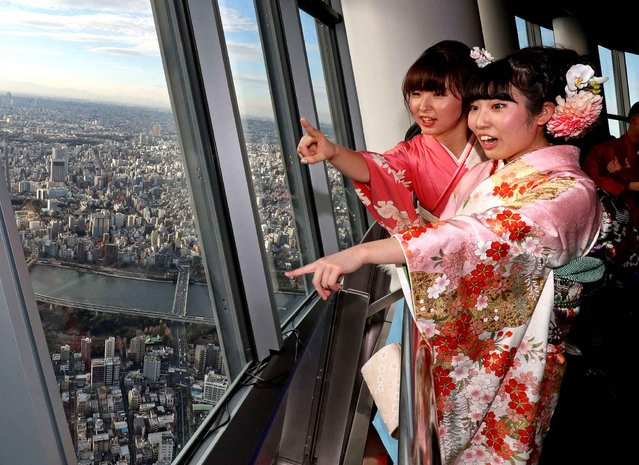 Kimono-clad women enjoy the view from Tokyo Sky Tree's 350-meter-high observation deck in Sumida Ward, Tokyo, on the Coming of Age Day, January 9, 2017. Sumida Ward invited about 430 local 20-year-old to the deck to celebrate them. Many city governments invite local 20-years-old to there's symbolic places and celebrate for their Coming of Age Day. (Photo by The Yomiuri Shimbun via AP Images)