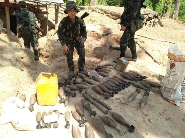 In this photo provided by Karen National Liberation Army, a Karen National Liberation Army soldier holds a motor shell while standing next to a cache of mortar shells found at a Myanmar military outpost Friday, May 7, 2021, in Mutraw district, Karen State, Myanmar. Ethnic Karen guerrillas burned down a Myanmar military outpost Friday morning, capturing it without a fight after its garrison fled at their approach, a senior Karen officer said. (Photo by Karen National Liberation Army via AP Photo)
