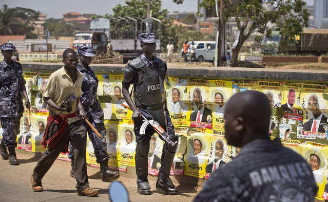 An armed Ugandan riot policeman patrols past campaign posters for long-time President Yoweri Museveni, as well as local members of Parliament, on a street in Kampala, Uganda Wednesday, February 17, 2016. (Photo by Ben Curtis/AP Photo)