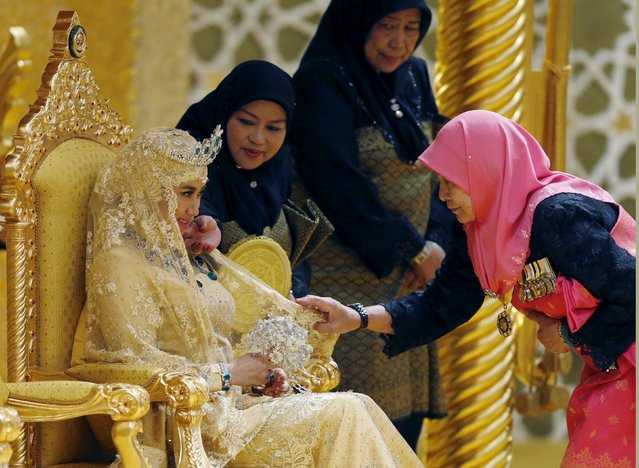 "Ladies-in-waiting adjust the veil of Dayangku Raabi'atul 'Adawiyyah Pengiran Haji Bolkiah as she waits for Prince Abdul Malik to arrive for the ""bersanding"" or enthronement ceremony at their wedding in the Nurul Iman Palace in Bandar Seri Begawan April 12, 2015. (Photo by Olivia Harris/Reuters)"