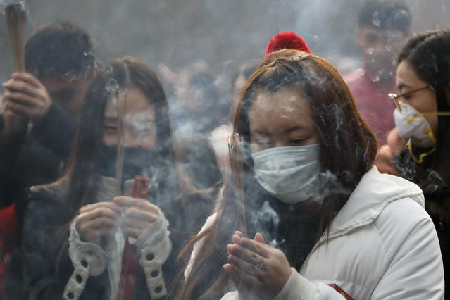 Chinese worshippers wearing masks burn incense while offering prayer at Beijing's Yonghegong Lama Temple as the Chinese capital is blanketed by heavy smog on the first day of the New Year, Sunday, January 1, 2017. (Photo by Andy Wong/AP Photo)