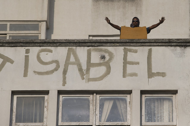 A squatter wearing foam for protection raises his arms as police stand below, during an eviction from the building people invaded about a week ago in the Flamengo neighborhood of Rio de Janeiro, Brazil, Tuesday, April 14, 2015. (Photo by Silvia Izquierdo/AP Photo)