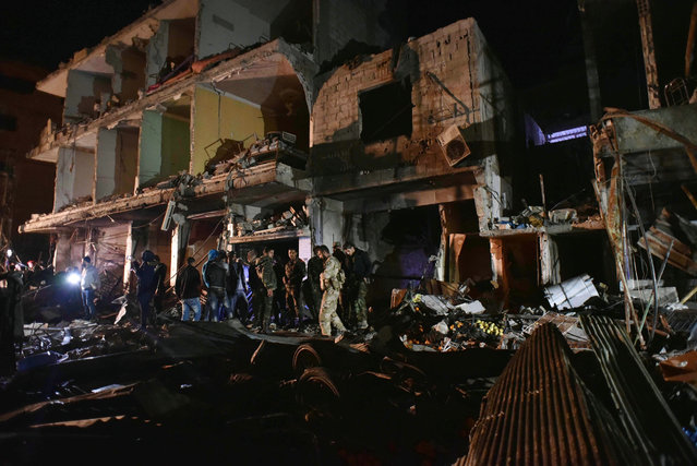 People gather in the aftermath of a multiple explosive attack in the Sayyida Zeinab area, 10 km south of Damascus, Syria, Sunday, February 21, 2016. (Photo by Natalia Sancha/AP Photo)