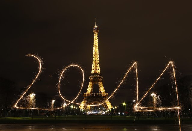 "A reveler writes ""2014"" with sparklers ahead of New Year's Eve, in front of the Eiffel Tower in Paris. (Photo by Benoit Tessier/Reuters)"