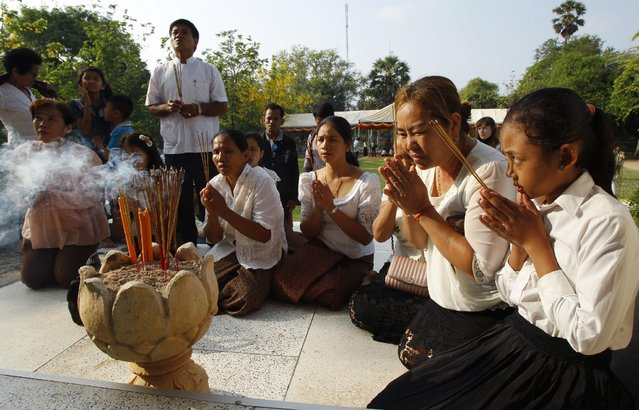Cambodians pray in front of a stupa containing hundreds of human skulls and bones of victims in Khmer Rouge regime, at Choeung Ek memorial on the outskirts of Phnom Penh, Cambodia, Friday, April 17, 2015. (Photo by Heng Sinith/AP Photo)