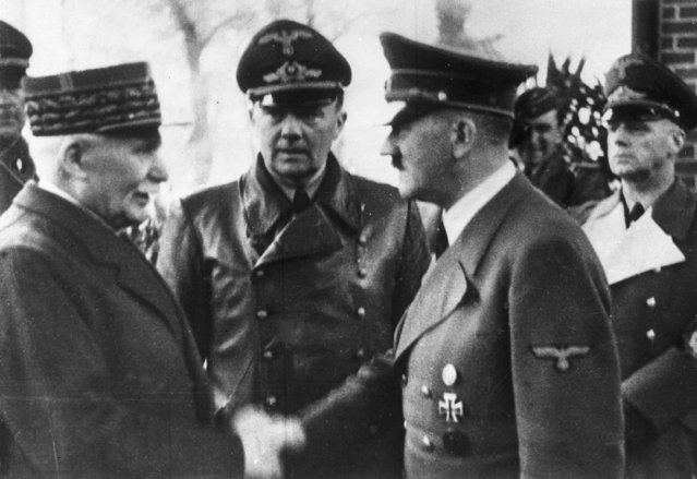 German Chancellor Adolf Hitler, right, shakes hands with Head of State of Vichy France Marshall Philippe Petain, in occupied France, October 24, 1940. Behind centre is Paul Schmidt an interpreter and right is German Minister of Foreign Affairs Joachim Von Ribbentrop. (Photo by AP Photo)
