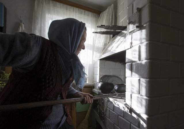 Nastia Pokolo, 74, puts a pot into a furnace at her house in the village of Babinets, southwest of the capital Minsk, April 17, 2015. (Photo by Vasily Fedosenko/Reuters)