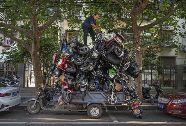 A worker piles salvaged e-bikes and scooters on the back of his three wheeler before taking them to be recycled on August 31, 2021 in Beijing, China. (Photo by Kevin Frayer/Getty Images)