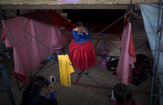 Young cholita wrestler Wara puts her makeup on before competing in the ring in El Alto, Bolivia, Sunday, February 24, 2019. Wara, 22, and the other trainees are still a year away from their full professional debuts while training in matches against the established athletes. (Photo by Juan Karita/AP Photo)