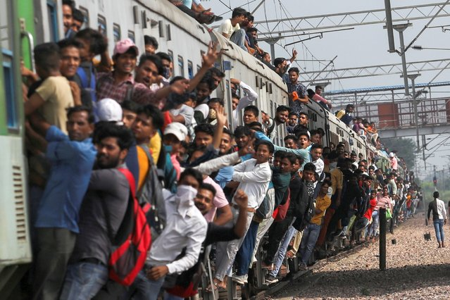 People cling on to a crowded train as it leaves a railway station during the ongoing Coronavirus Disease (COVID-19) outbreak in Ghaziabad, India, September 21, 2021. (Photo by Anushree Fadnavis/Reuters)