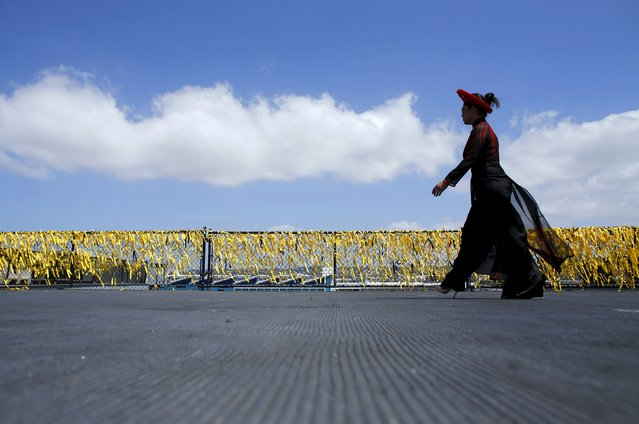 In traditional dress, a member of the Vietnamese community attends a ceremony on the flight deck of the USS Midway as the ship hosts a commemoration of the 40th Anniversary of Operation Frequent Wind and the fall of Saigon in San Diego, California, United States April 26, 2015. Volunteers tied 58,300 yellow ribbons on a fence surrounding the Midway's flight deck to signify U.S. deaths in the conflict. (Photo by Mike Blake/Reuters)