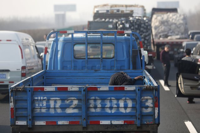 A man takes a nap in a truck as cars stop on Jinji Expressway located between Beijing and Tianjin, in a heavy traffic jam in Tianjin, China, March 2, 2016. (Photo by Kim Kyung-Hoon/Reuters)