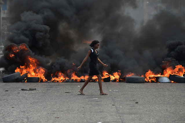 A woman walks past tire barricades set ablaze by demonstrators on the fourth day of protests in Port-au-Prince, February 10, 2019, against Haitian President Jovenel Moise and misue of Petrocaribe fund. (Photo by Héctor Retamal/AFP Photo)