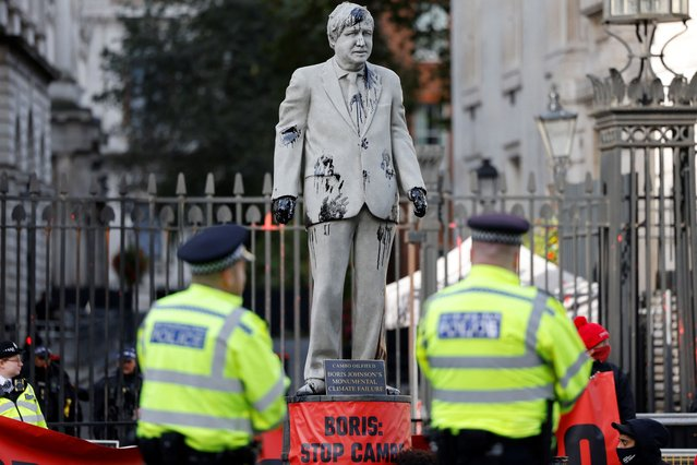 Police officers stand guard as Greenpeace activists stage a sit-in after installing an oil-splattered statue of British Prime Minister Boris Johnson by artist Hugo Farmer at Downing Street in London on October 11, 2021 during a protest against the Cambo oil field project in the Shetland Islands. (Photo by Tolga Akmen/AFP Photo)