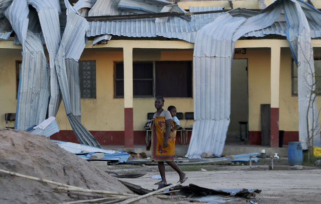 A woman carrying a baby on her back walks past damaged school in Beira, Mozambique, Monday, March 25, 2019. The United Nations is making an emergency appeal for $282 million for the next three months to help Mozambique start recovering from the devastation of Cyclone Idai. (Photo by Themba Hadebe/AP Photo)