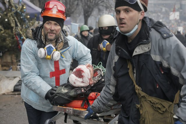 Activists  evacuate a wounded protester during clashes with police in Kiev's Independence Square, the epicenter of the country's current unrest, Kiev, Ukraine, Thursday, February 20, 2014. (Photo by Efrem Lukatsky/AP Photo)