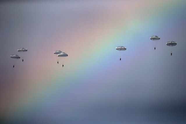 """Russian paratroopers jump past rainbow from an IL-76 transport plane during a joint Serbian-Russian military training exercise """"Slavic Brotherhood"""" in the town of Kovin, near Belgrade, Serbia November 7, 2016. (Photo by Marko Djurica/Reuters)"""