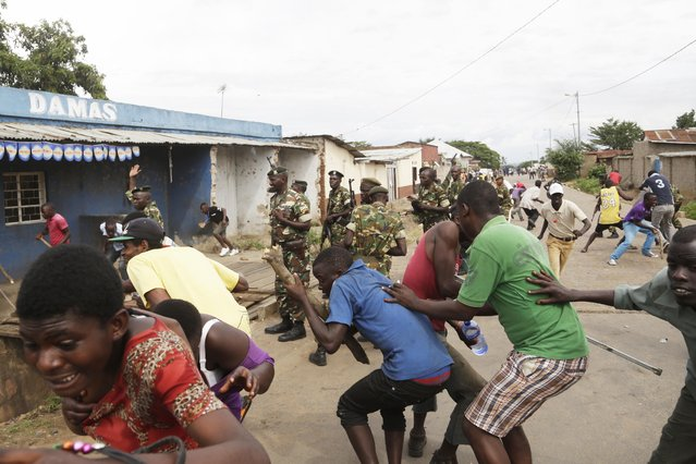 Demonstrators duck and run from soldiers firing into the air to disperse a crowd of demonstrators who had cornered  Jean Claude Niyonzima a suspected member of the ruling party's Imbonerakure youth militia in a sewer in the Cibitoke district of Bujumbura, Burundi, Thursday May 7, 2015. (Photo by Jerome Delay/AP Photo)