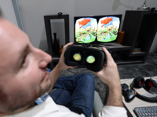 """Paul Bettner, co-founder of Playful Corp which created the new """"Lucky's Tale"""" game for Oculus Rift, tries on the Oculus VR Inc. Rift Development Kit 2 (DK2) headset to play """"Lucky's Tale"""" at the 2014 Electronic Entertainment Expo, known as E3, in Los Angeles, California June 11, 2014. (Photo by Kevork Djansezian/Reuters)"""