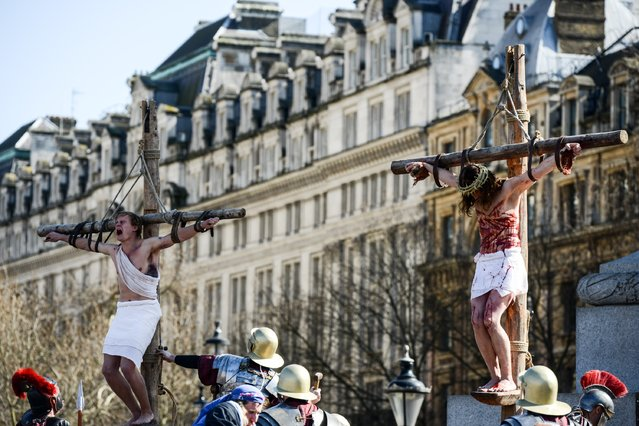 "Actor James Burke-Dunsmore is lowered from a crucifix whilst playing Jesus during The Wintershall's ""The Passion of Jesus"" in front of crowds on Good Friday at Trafalgar Square on March 25, 2016 in London, England. (Photo by Chris Ratcliffe/Getty Images)"