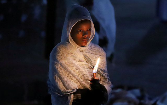 An Ethiopian Orthodox faithful holds candles during the Easter eve prayers at the Holy Trinity Cathedral Orthodox church in Addis Ababa, Ethiopia, April 28, 2019. (Photo by Tiksa Negeri/Reuters)