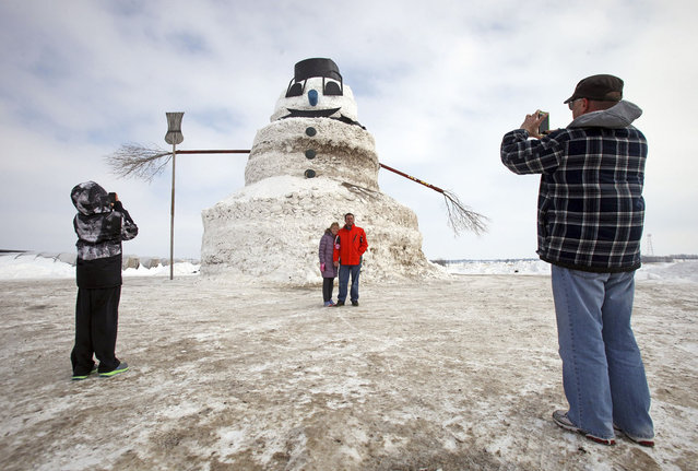 "Kevin and Merith Starren have their picture taken by Merith's brother Mark Ernst (R) and nephew Logan Ernst (L) in front of a 50-foot snowman named ""Granddaddy"" in Gilman, Minnesota, March 6, 2014. (Photo by Eric Miller/Reuters)"