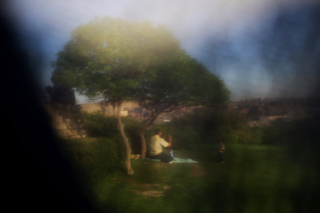 This Friday, May 8, 2015 image shows a father taking the photograph of his son at Al-Azhar Park, one of the bustling city's few public parks, in Cairo, Egyp. (Photo by Hassan Ammar/AP Photo)