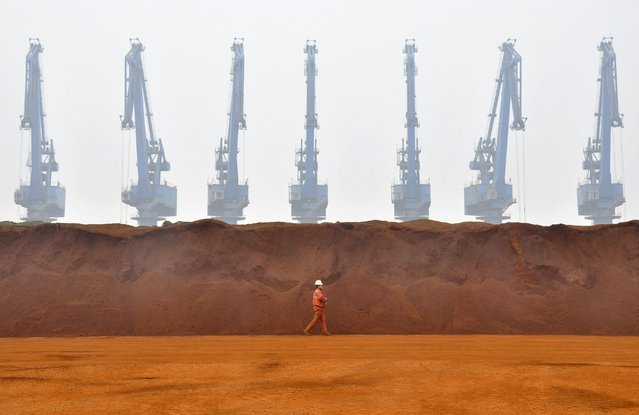 A worker walks past a pile of iron ore from Australia at a port in Tianjin municipality in this March 29, 2010 file photo. (Photo by Vincent Du/Reuters)