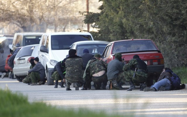 Members of pro-Russian self-defence units take cover behind cars outside a military base in the Crimean town of Belbek near Sevastopol March 22, 2014. (Photo by Vasily Fedosenko/Reuters)