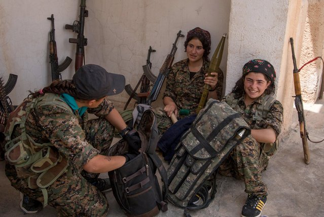Armed Kurdish female fighters from People's Protection Units (YPG) talk to each other in the Assyrian village of Tel Nasri, western of Tel Tamr town, after the YPG said they retook control of the area from the Islamic State, May 21, 2015. (Photo by Rodi Said/Reuters)