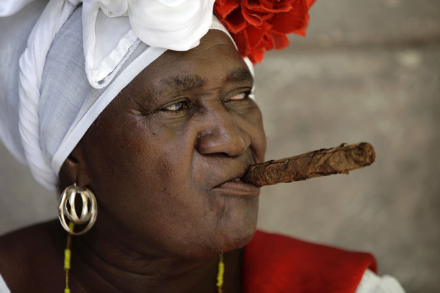 "Street entertainer and fortune teller ""Juana La Cubana"" holds a cigar in her mouth as she waits for tourists in Havana, Cuba, Sunday, May 24, 2015. Juana is 72 years old and has worked in the Cathedral square in Old Havana for 28 years. (Photo by Desmond Boylan/AP Photo)"