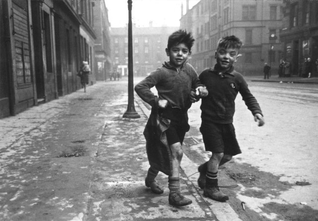 Two boys in the Gorbals area of Glasgow, UK on January 31, 1948. The Gorbals tenements were built quickly and cheaply in the 1840s, providing housing for Glasgow's burgeoning population of industrial workers. Conditions were appalling; overcrowding was standard and sewage and water facilities inadequate. The tenements housed about 40,000 people with up to eight family members sharing a single room, 30 residents sharing a toilet and 40 sharing a tap. By the time this photograph was taken 850 tenements had been demolished since 1920. Redevelopment of the area began in the late 1950s and the tenements were replaced with a modern tower block complex in the sixties. (Photo by Bert Hardy/Getty Images)