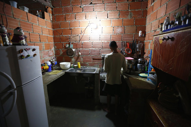 """Francisco, 18, cooks in his apartment inside the """"Tower of David"""" skyscraper in Caracas February 9, 2014. (Photo by Jorge Silva/Reuters)"""