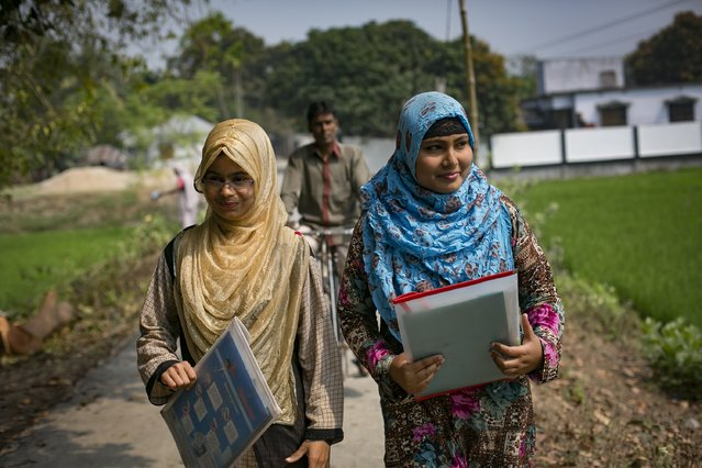 Rani (blue scarf) walks with a friend with her father following on a bicycle to catch a rickshaw to take a school exam March 6, 2017 in Khulna division, Bangladesh. (Photo by Allison Joyce/Getty Images)