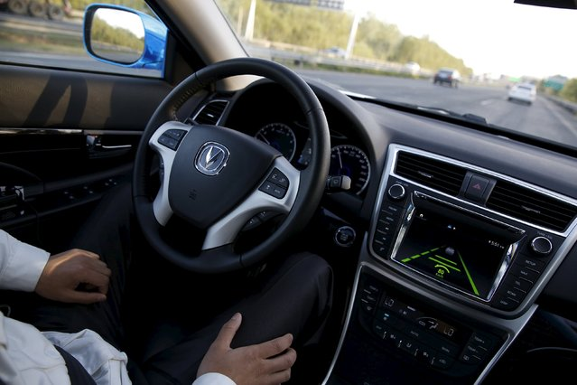 Li Zengwen, a development engineer at Changan Automobile, removes his hands from the steering wheel while the car is on self-driving mode during a test drive on a highway in Beijing, China, April 16, 2016. (Photo by Kim Kyung-Hoon/Reuters)