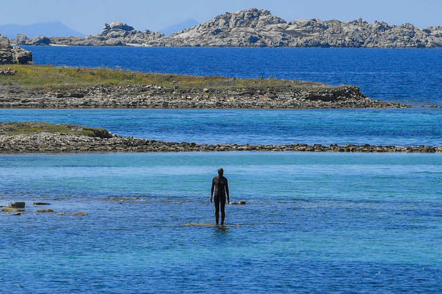 """The statue """"6 times left"""" by renowned British artist Antony Gormley, and part of his exhibition """"Sight"""" stands in the sea at the entrance od the port of the island of Delos, a UNESCO World Heritage Site, on May 3, 2019. Near the Greek island of Mykonos, in the Cyclades, the uninhabited island of Delos, known for its archaeological riches, hosts for the first time on an ancient Greek site an exhibition of contemporary art: 29 sculptures by the British artist Antony Gormley. The exhibition will run until October 30, 2019. (Photo by Louisa Gouliamaki/AFP Photo)"""