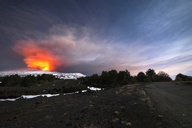Mount Etna, Europe's most active volcano, is seen from the side of a road as it spews lava during an eruption in the early hours of Thursday, March 16, 2017. Sicily's Mount Etna volcano unleashed an explosion Thursday, hurling molten rocks and steam that rained down on tourists, journalists and a scientist who scrambled to escape the barrage. Ten people were reported injured. The tourists, who were drawn to Etna to observe the spectacle of the active volcano erupting, were caught by surprise when its flowing magma hit thick snow, causing a phreatic explosion that rained rock and other material down upon them. Mount Etna has been active for the past two days, creating a visual spectacle as it spews lava and ash into the air. A new lava flow started from the southeastern crater on Wednesday, and was advancing with a temperature above 1,000 degrees Centigrade (1,832 degrees Fahrenheit) in an area covered by snow, creating the explosion. A similar phreatic explosion, caused when lava hits water, on Etna in 2002 injured 32 people, mostly firefighters and other emergency workers responding to a series of eruptions. Authorities limited access to riskier areas on Mount Etna following a deadly eruption in 1979 that killed nine tourists who were standing at the volcano's rim. Reports indicate that the tourists who experienced the eruption Thursday were in a zone where access is permitted with a guide. The volcanology institute said it was continuing to monitor the situation. (Photo by Salvatore Allegra/AP Photo)
