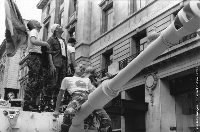 A reveller at London's annual Lesbian and Gay Pride Festival and March straddles a tank's gun barrel as it parades through London, 24th June 1995