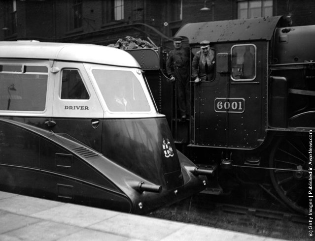 1933: Two men driving an old 250-ton steam engine admire the new 135-ton streamlined Cornish Riviera Express engine on the track beside them
