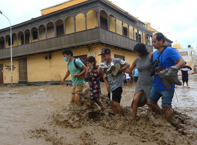 Local residents wade through the water as a flash flood hits the city of Trujillo, 570 kilometres north of Lima on March 18, 2017, bringing mud and debris. (Photo by Celso Roldan/AFP Photo)